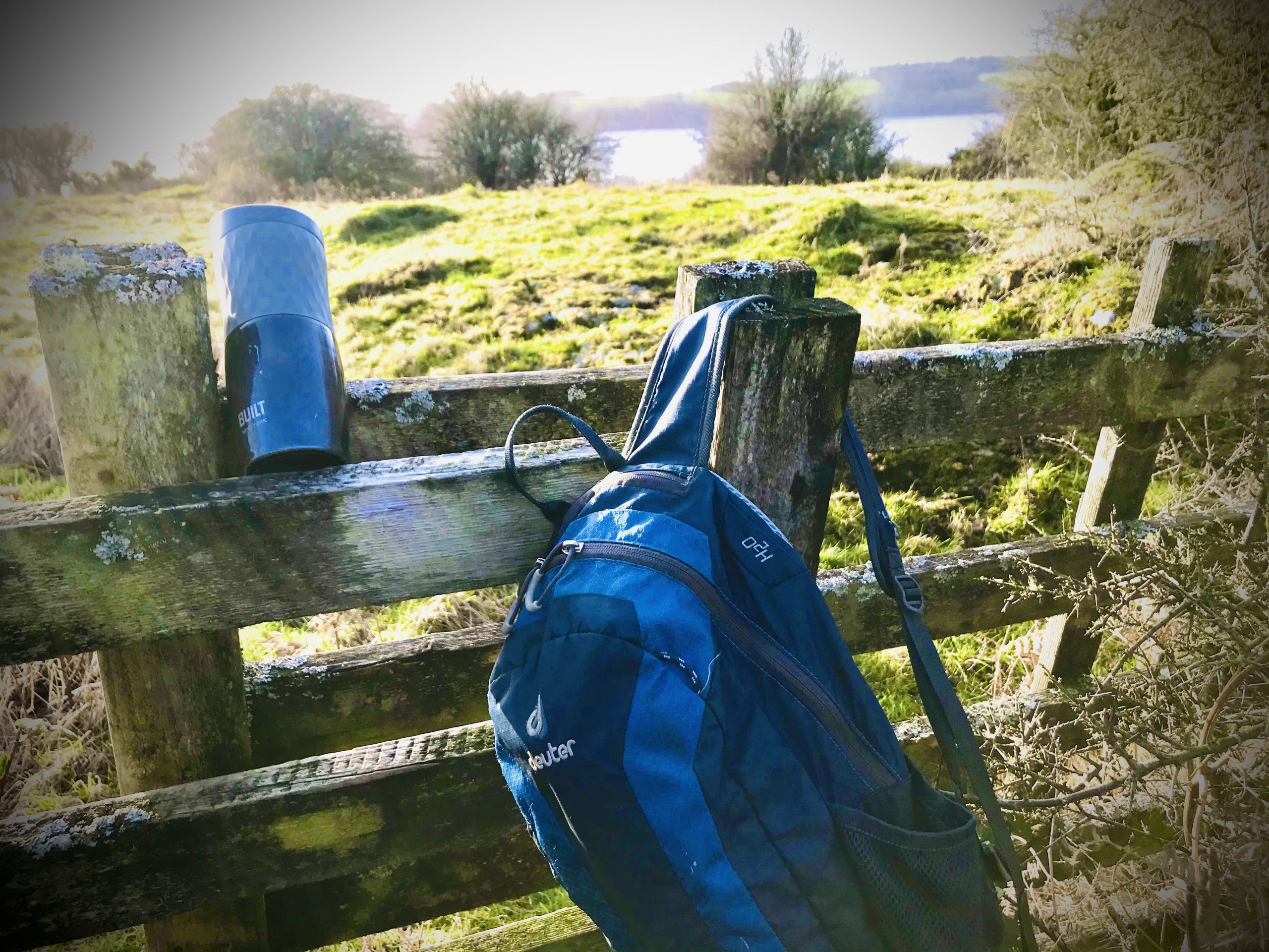 Coffee Flask and Rucksack on a gate