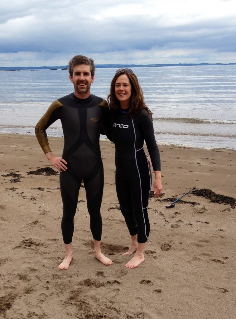 Couple in wetsuits on a beach