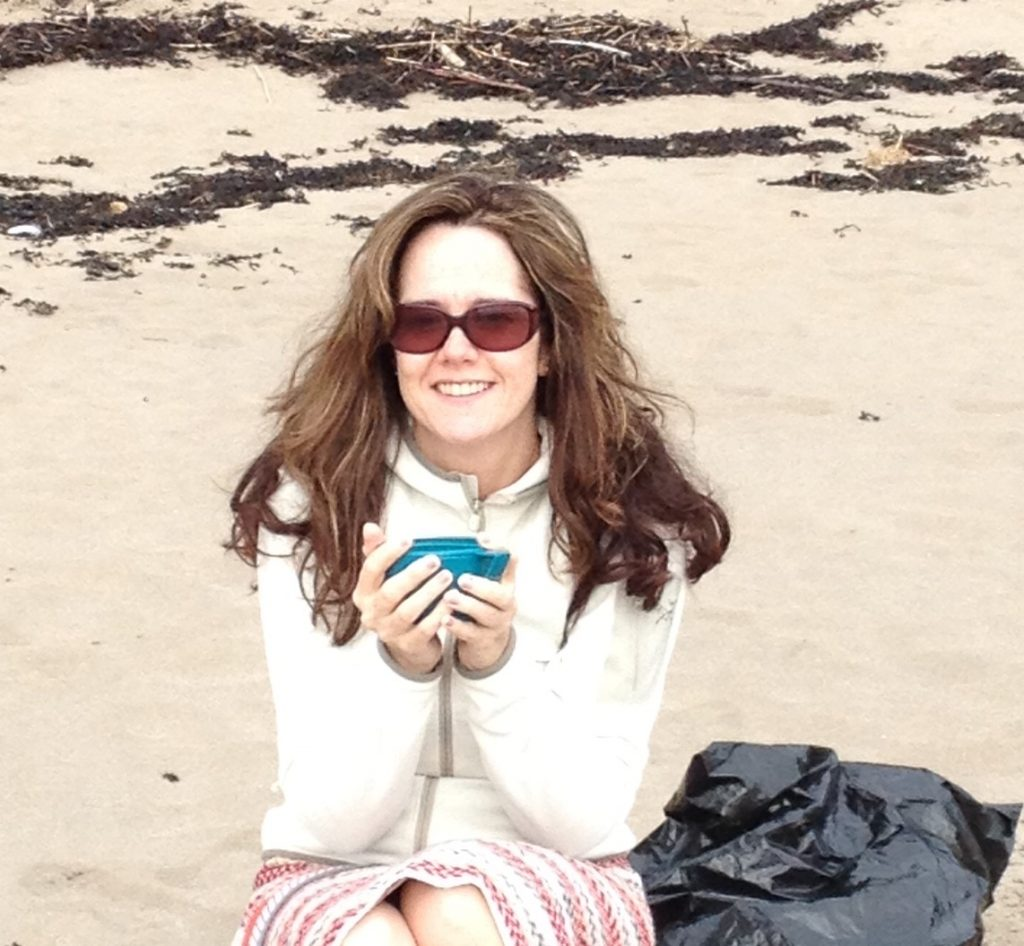 Woman holding a cup of coffee on the beach