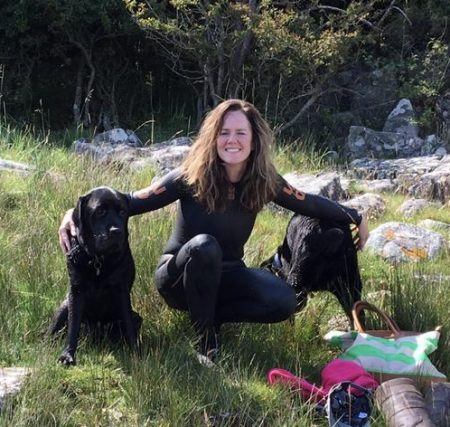 Woman in wetsuit on a beach with dogs